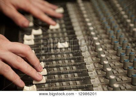 produtor de som movendo as modas do painel do mixer de som sujo. concentrar-se nos dedos da mão direita
