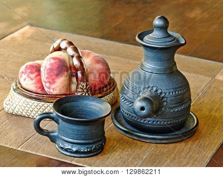 Arabian style coffee pot and peaches in ceramic vase on a table.