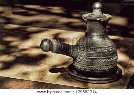 Black ceramic arabian style coffee pot on wooden table and spots of sunlight.