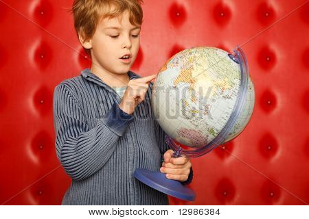 Boy pointing finger on globe. Portrait on red?leather wall. Horizontal format.