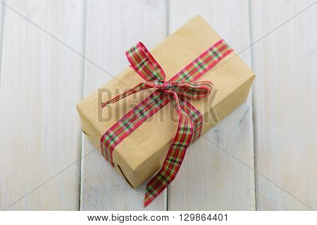 Box with a gift on a wooden table tied with red ribbon.
