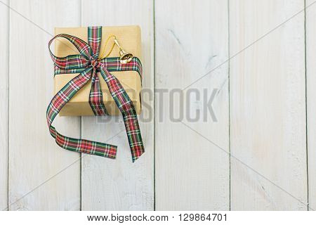 Box with a gift on a wooden table tied with ribbon and decorated with a small golden bell.