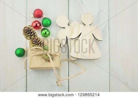 small box on a light wooden background tied with a rope decorated with a sprig of Christmas trees Christmas balls and angels.