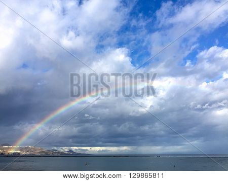 A shot of a rainbow in the beach in a stormy day