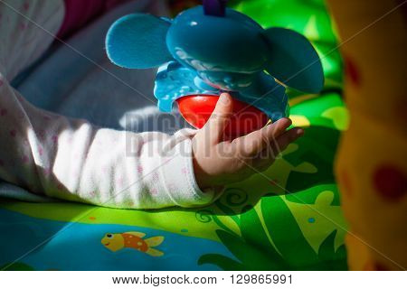 Baby Hand Playing with colorful elefant toys.