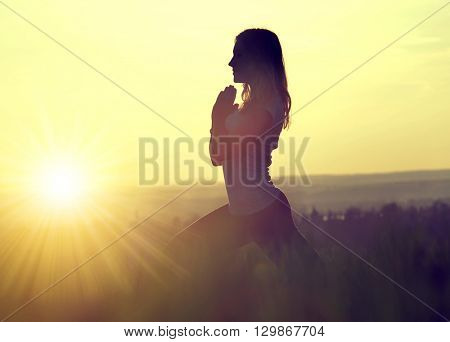 Silhouette of a woman meditating on a meadow at sunset
