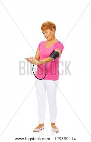 Smiling senior woman measuring blood pressure