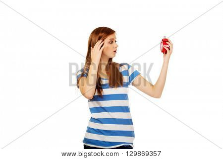 Shocked teenage woman with alarm clock