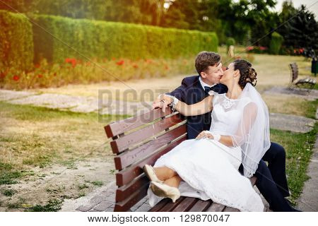 Newlyweds Kissing At Bench In Park.