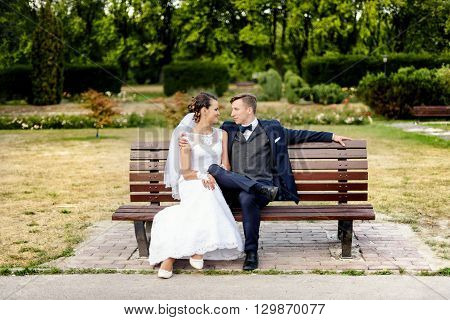 Newlyweds Sitting At Bench In Park