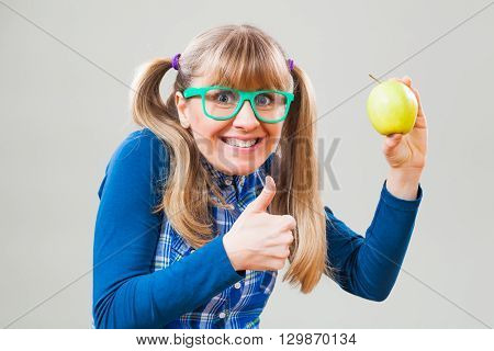 Studio shot portrait of happy nerdy woman who is holding an apple