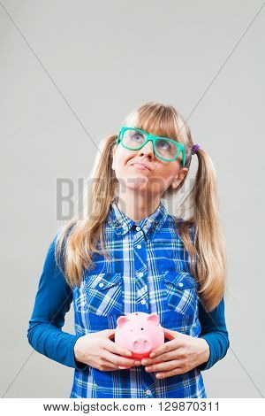 Studio shot portrait of nerdy woman who is holding piggy bang and thinking about ideas for making money.