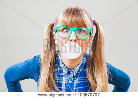Studio shot portrait of nerdy woman who is blowing bubble gum.