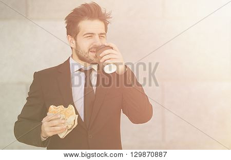 Closeuptoned picture of businessman eating junk food and drinkig tea or coffee while walking to office along street. Happy freelancer in hurry.