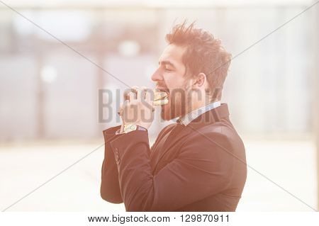 Closeup toned picture of businessman eating junk food on street while walking to office. Freelance man hurrying to work.