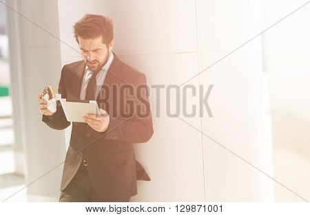 Toned picture of businessman standing near office building and looking at tablet PC. Handsome man eating junk food on street.