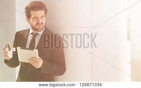 Toned picture of young businessman in business suit looking away and posing with tablet PC while eating junk food on street.
