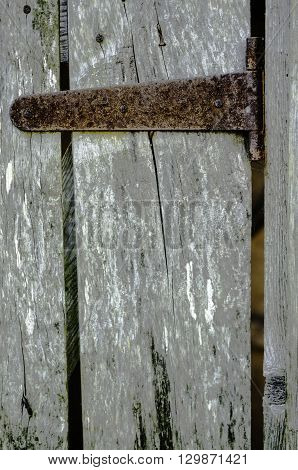 Rusty hinge on the door of the old boards.