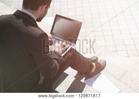 Closeup toned picture of businessman in black busness suit using laptop computer in city centre. Handsome man is freelancer.