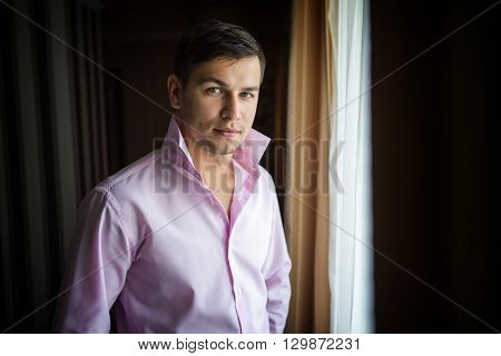 groom wearing a shirt in the window on the wedding day