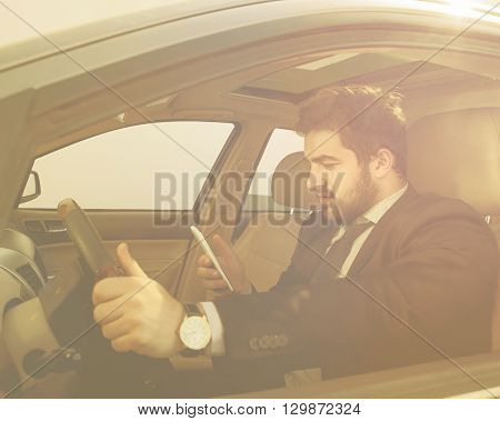 Toned image of young businessman driving car and looking at mobile or smart phone's screen. Freelance man in black business suit working on to go.