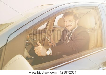 Toned picture of happy smiling businessman driving car and holding mobile or smart phone in front of him. Handsome freelance man working on to go.