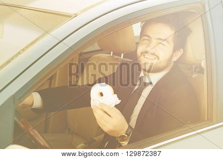 Toned picture of happy businessman eating doughnut and driving car to his office. Freelance man in black business suit smiling.