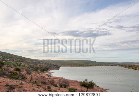 Elevated views over the Murchison River landscape with native flora on rocky coastal dunes under a blue sky with clouds at dusk in Kalbarri, Western Australia.