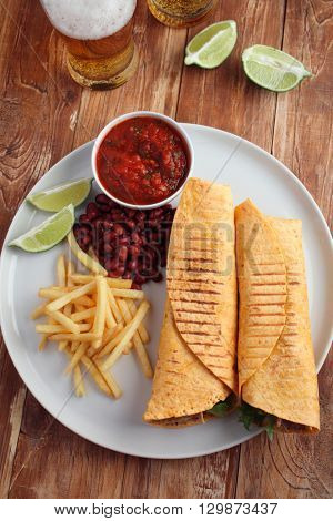 Chicken burritos with French fries, red bean, salsa sauce, and beer