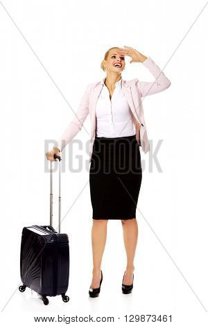 Business woman with wheeled suitcase covering eyes with hand