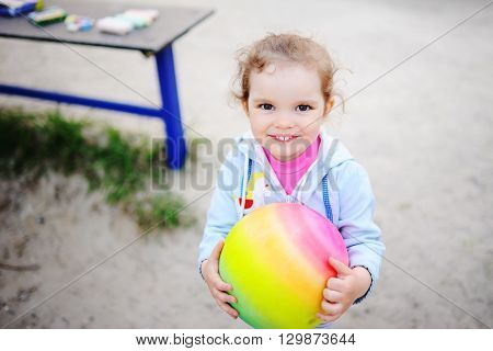 baby girl playing with a colored ball in the playground.Children's kind eyes