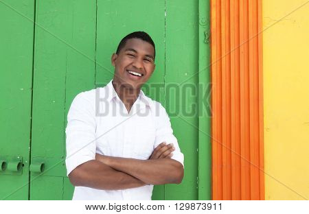 Friendly caribbean guy in front of a colorful wall laughing at camera