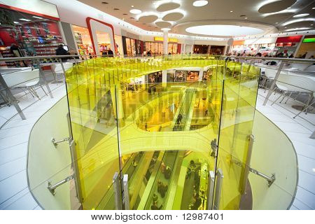 Escalator, stores, cafe, snack-bar and many buyers and customers in shopping center