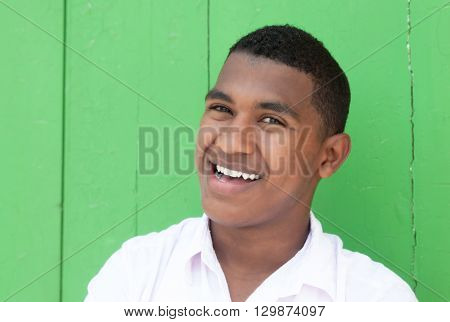 Happy caribbean guy in front of a green wall laughing at camera