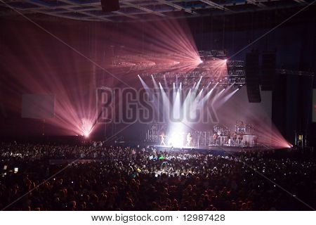 musical performance concert. light show. group band singer is performing dancing on stage. bright lights above stage