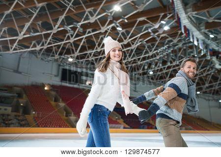 Smiling young couple at skating rink