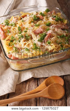 Casserole Noodles With Ham And Parmesan Close-up In A Glass Baking Dish. Vertical