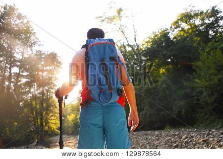 Man hiking with backpac and sticks in mountains in sunset. No effects - real sun