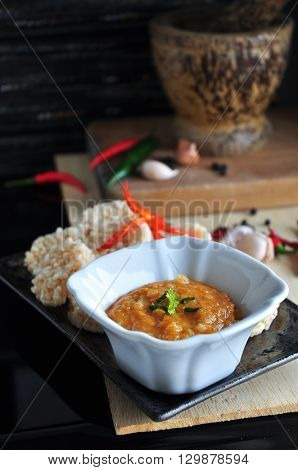 Thai food rice cracker and spicy dip sauce with ingredients and mortar on background