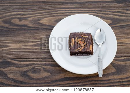 Homemade chocolate brownie with almond and spoon in white dish on wood table.