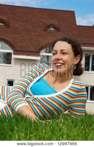Happy girl on lawn in front of new home. Smiling, she looks into distance.