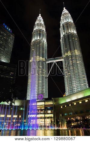 KUALA LUMPUR MALAYSIA - FEBRUARY 29: Night scene of Petronas twin towers with rainbow fountain on February 29 2016 in Kuala Lumpur Malaysia. The famous landmarks of Malaysia.