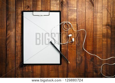 Blank clipboard on vintage wooden background. Clipboard with a blank sheet of white paper pencil and headphones. Mock-up for branding identity for designers. Top view.