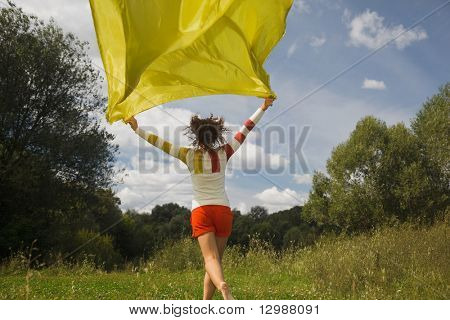 young woman in sunny summer day running with yellow fabric in hand, whiffle fabric
