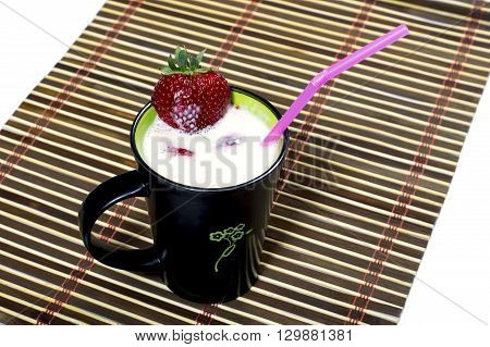 milk cocktail in a black mug is decorated with strawberry on a rug a subject drinks