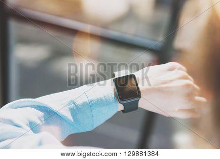 Photo Woman Working Modern Loft Studio.Girl Enjoying Generic Design Smart Watch.Looking Screen Smartwatch.Free Time Management. Horizontal. Burred background. Film and bokeh effects.