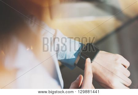 Photo Woman Relaxing Modern Loft Studio and Using Generic Design Smart Watch.Female Hands Touching Screen Smartwatch.Manage Free Time Process. Horizontal mockup. Burred background. Film effects.