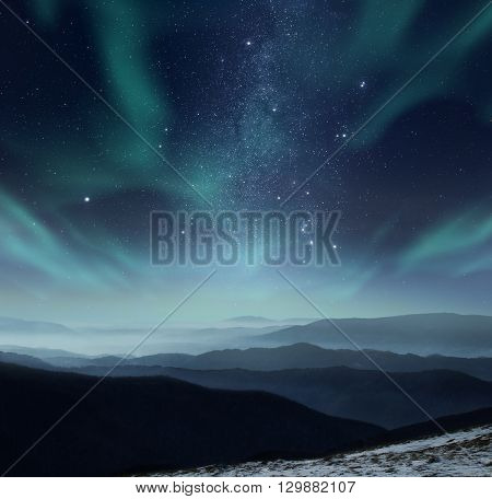 Starry night sky with aurora polaris over the mountains
