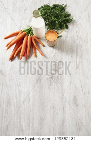 Isolated Top View On Wooden Table, Farm Carrot Harvest Lying Near Bottle And Glass Filled With Mix N