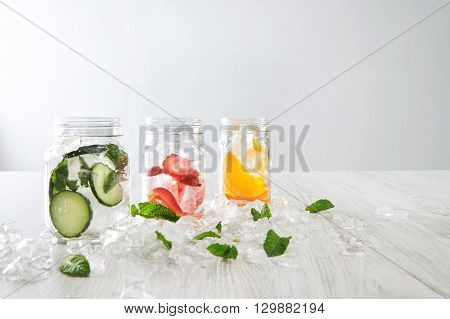 Closeup Rustic Jars In Crashed Ice Cubes With Orange,strawberry,cucumber And Mint Prepared To Make F